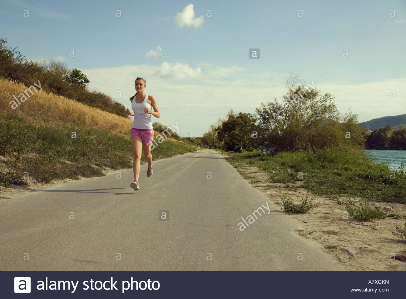 Young female jogger running along riverside - Stock Image