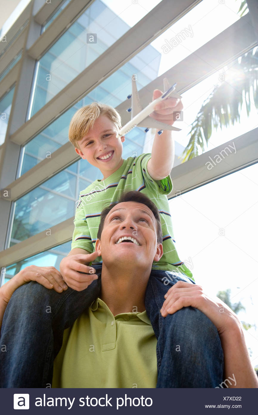 Father carrying son  on shoulders in airport, boy holding toy aeroplane, smiling, front view, low angle view lens flare Stock Photo