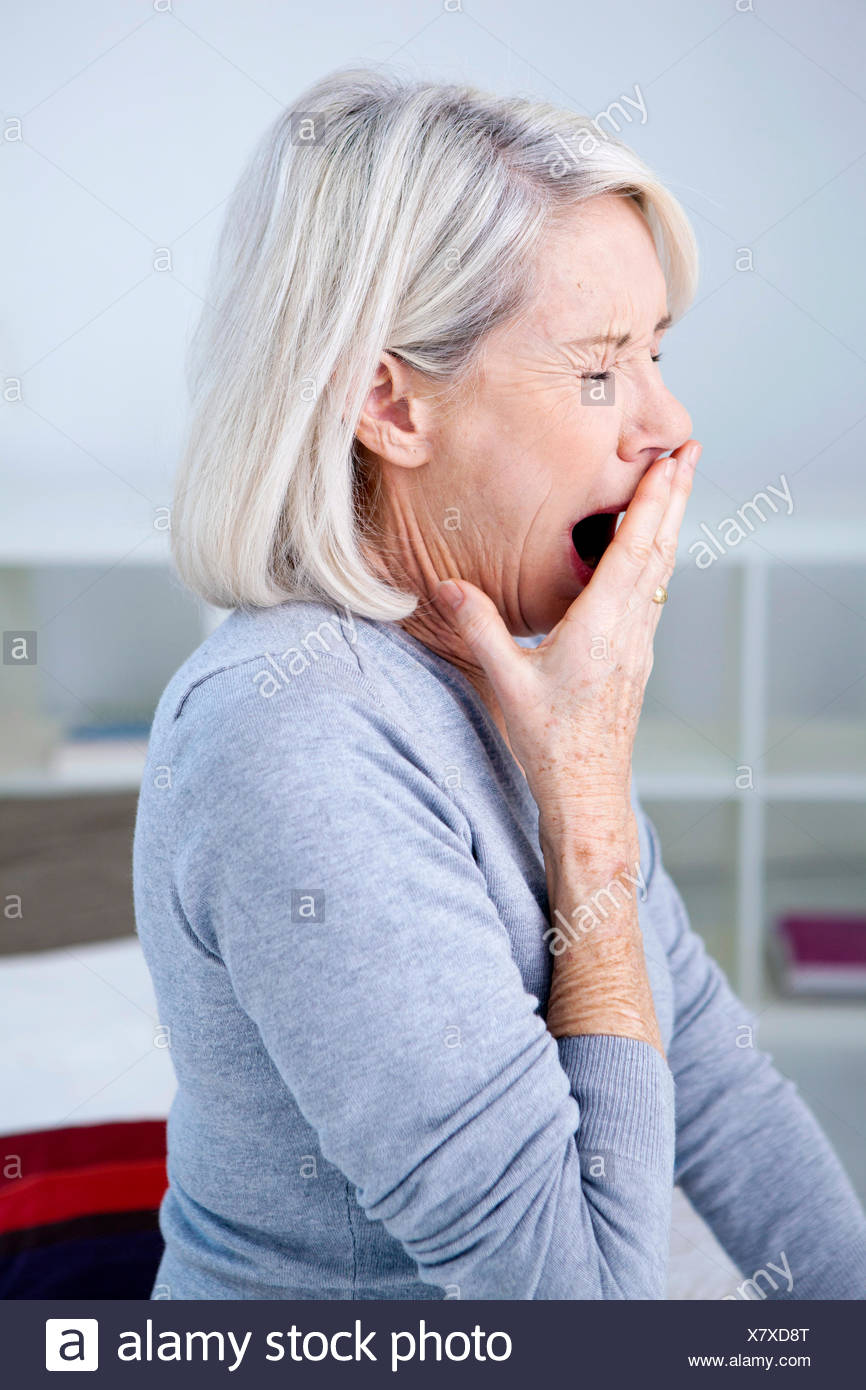 Elderly person yawning - Stock Image