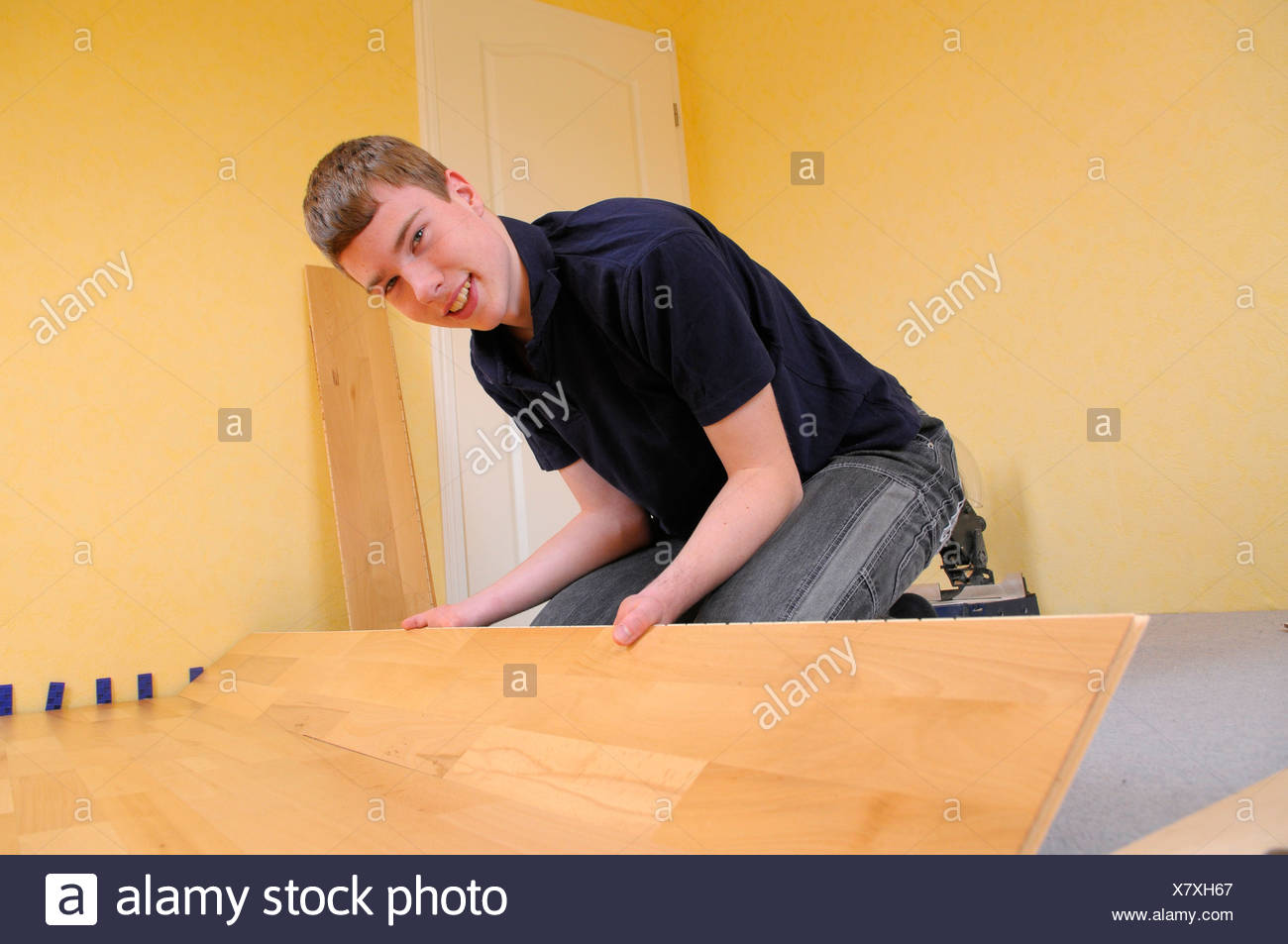 Teenager laying parquet flooring Stock Photo