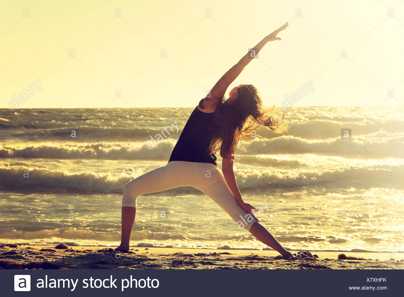 Woman practising reverse warrior pose on beach - Stock Image