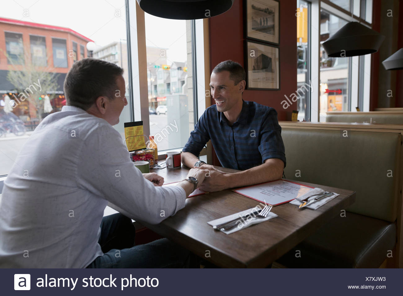 Affectionate male gay couple holding hands at diner booth - Stock Image