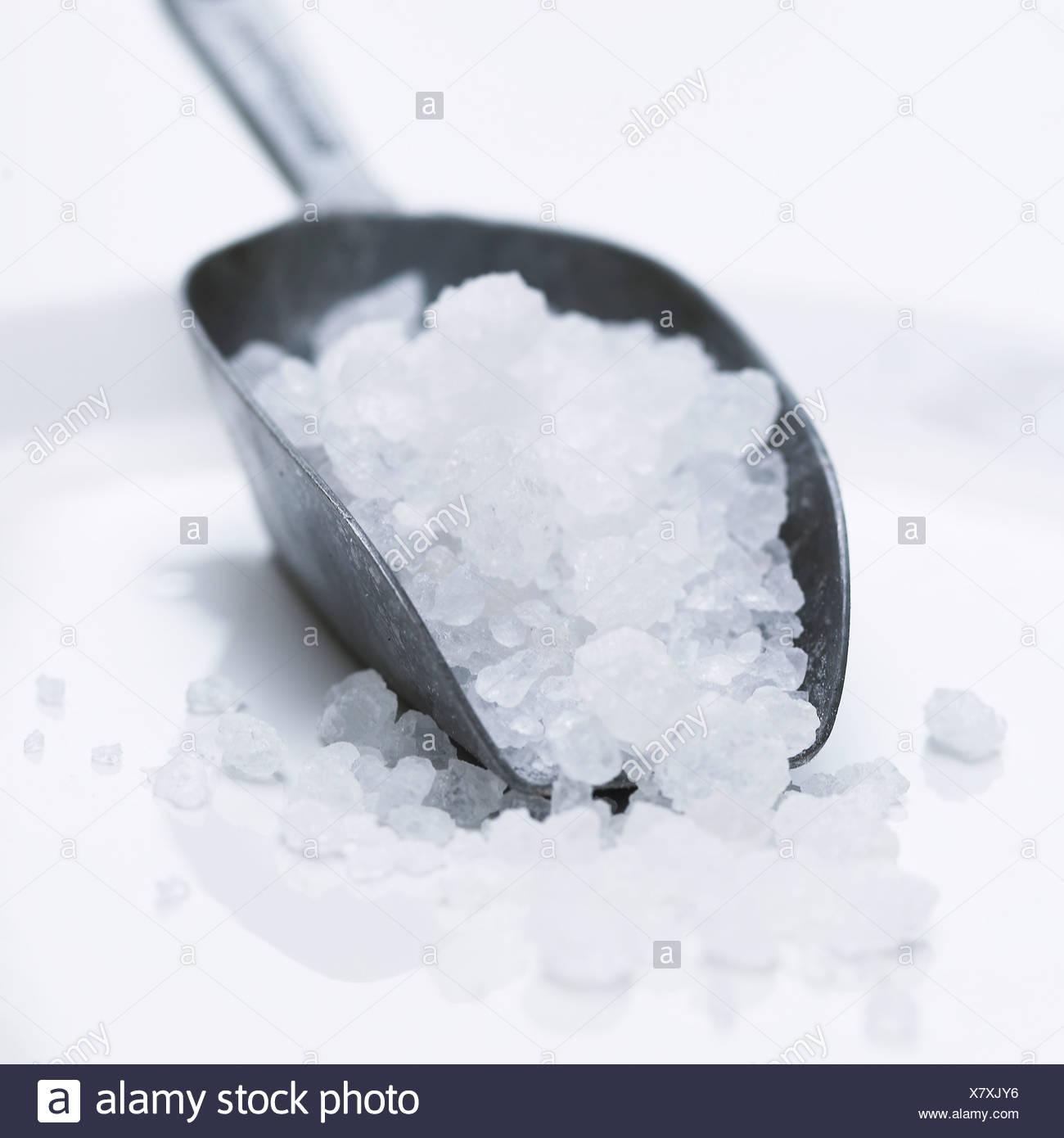 Rock salt in a salt scoop - Stock Image