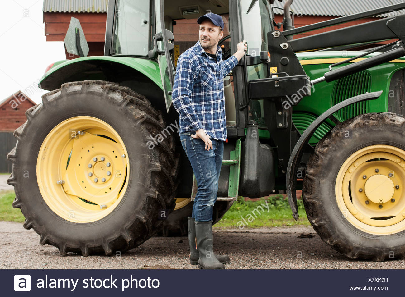 Full length of farmer standing by tractor on farm - Stock Image