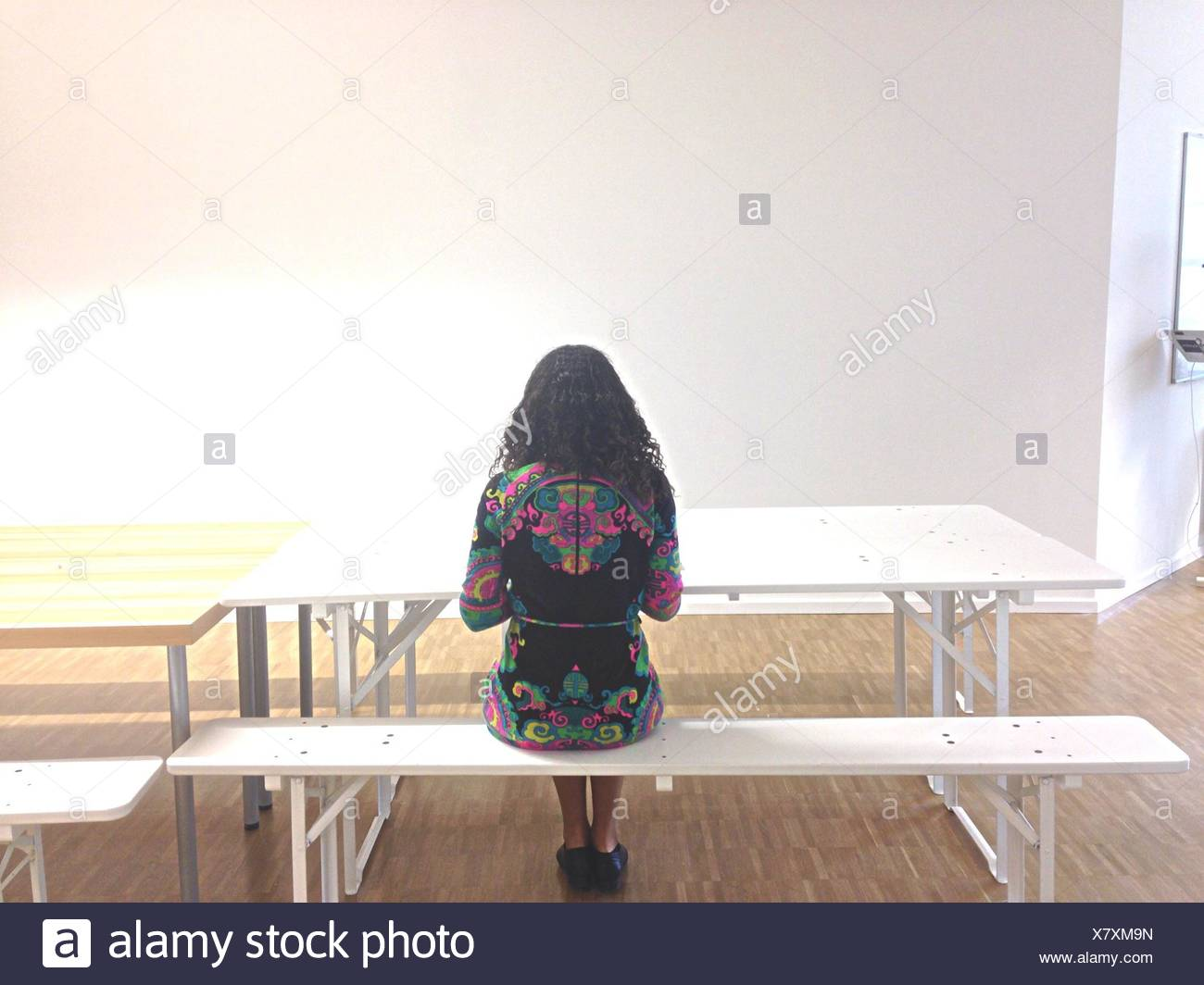 Full Length Rear View Of Young Woman Sitting In Cafeteria - Stock Image