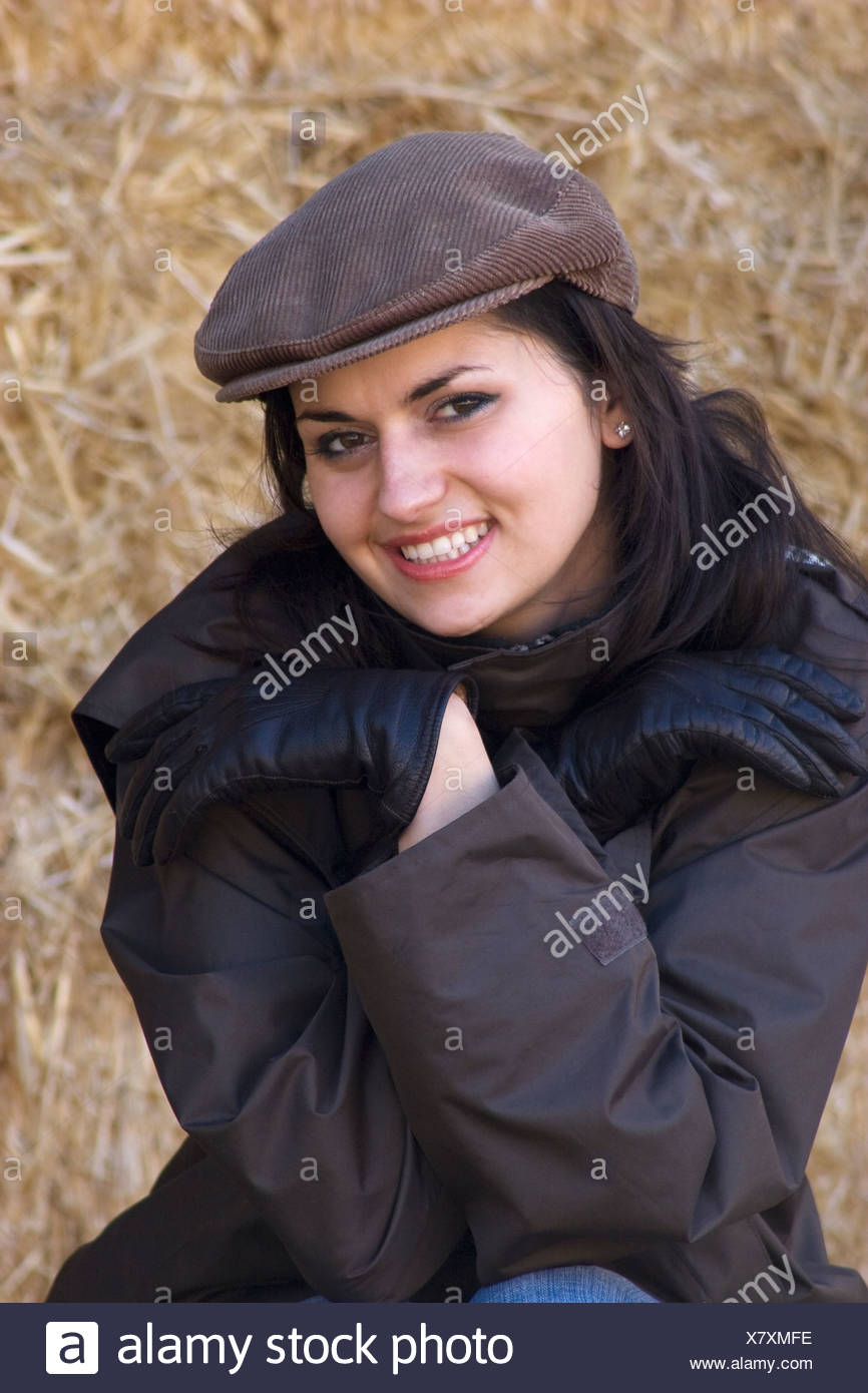 4abe08dfddc15 portrait modern young woman sitting in barn dresssed in brown raincoat and  corduroy cap