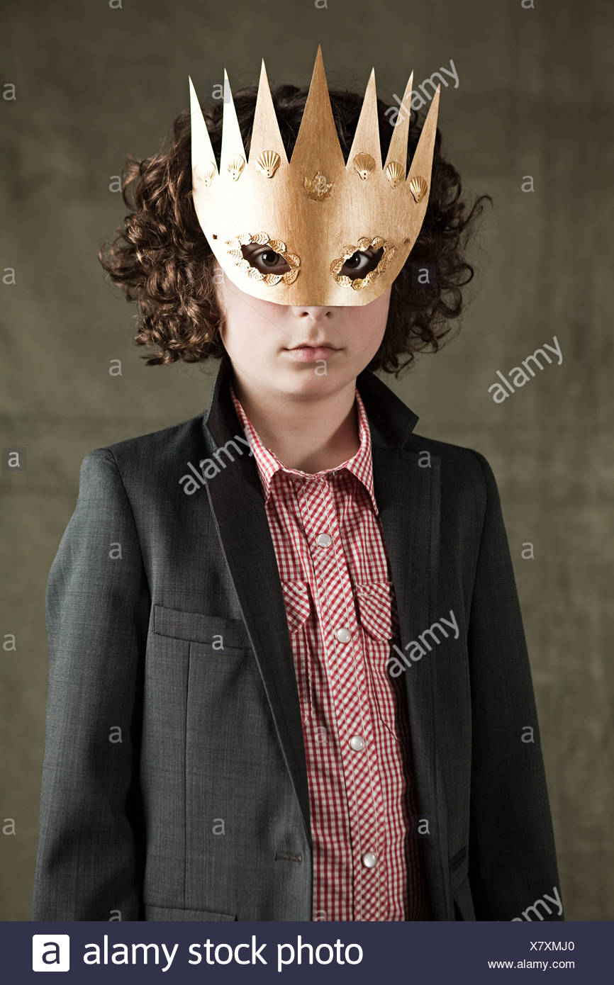 Young boy wearing gold crown mask - Stock Image