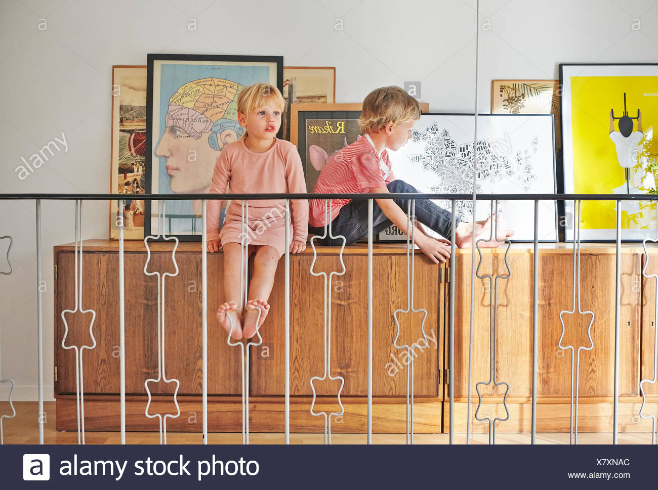 Girl and boy sitting on cupboard with pictures behind railing - Stock Image