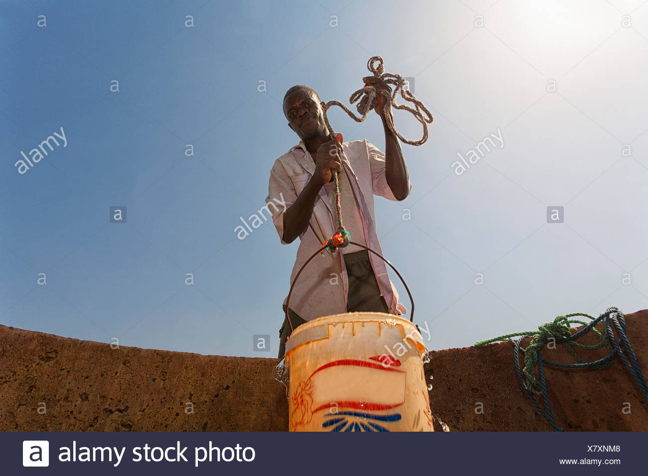 man fetching water from a well in the sahel region of the Senegal river, Senegal - Stock Image