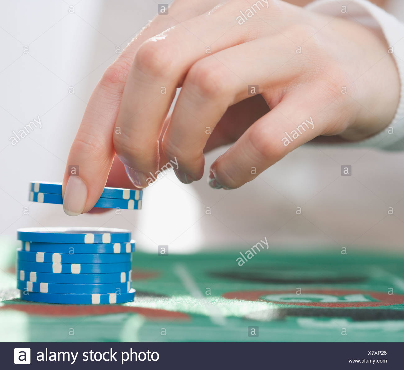 Woman picking up poker chips - Stock Image