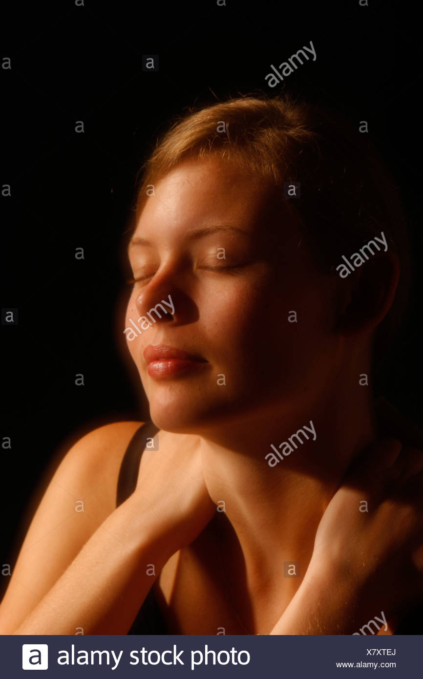 Young woman with her hands on her bare shoulders, portrait - Stock Image