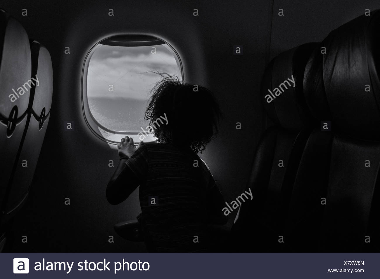 Rear view of a girl looking out of the window on a plane - Stock Image