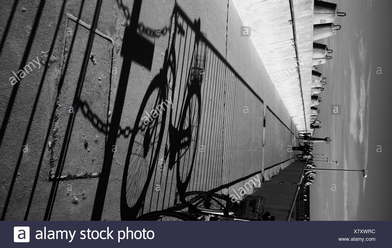 Shadow Of Bicycle Parked On Sidewalk Against Sky - Stock Image