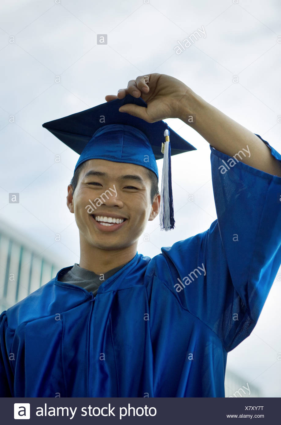 Male graduate with hand on cap - Stock Image
