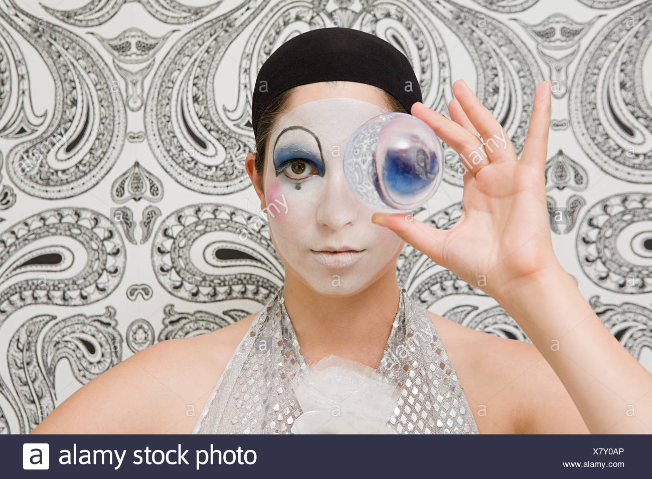 Clown looking through a crystal ball - Stock Image
