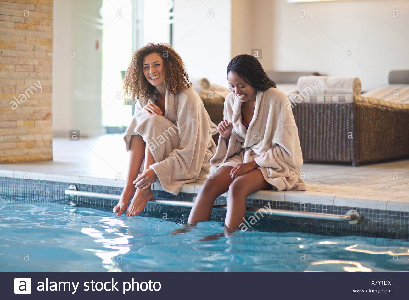 Two young women relaxing on edge of spa swimming pool Stock Photo