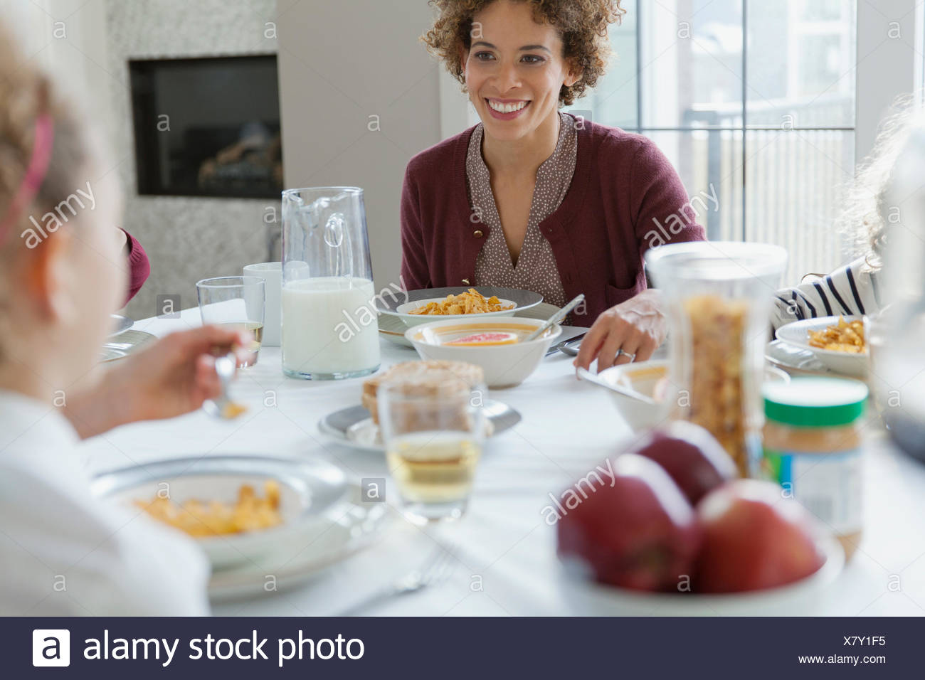 Mother looking at daughter across breakfast table. - Stock Image