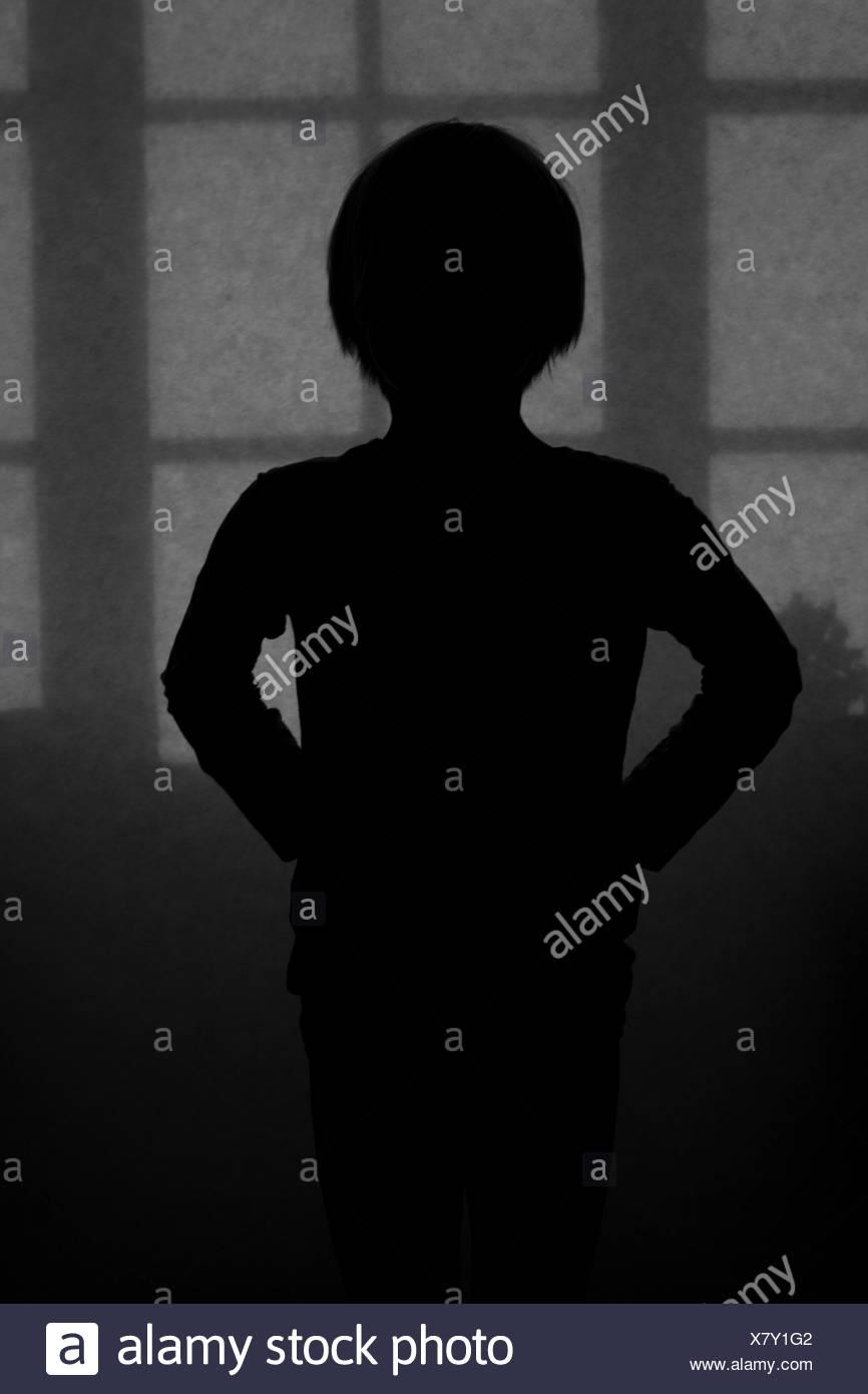 Sweden, Silhouette of boy in dark room - Stock Image