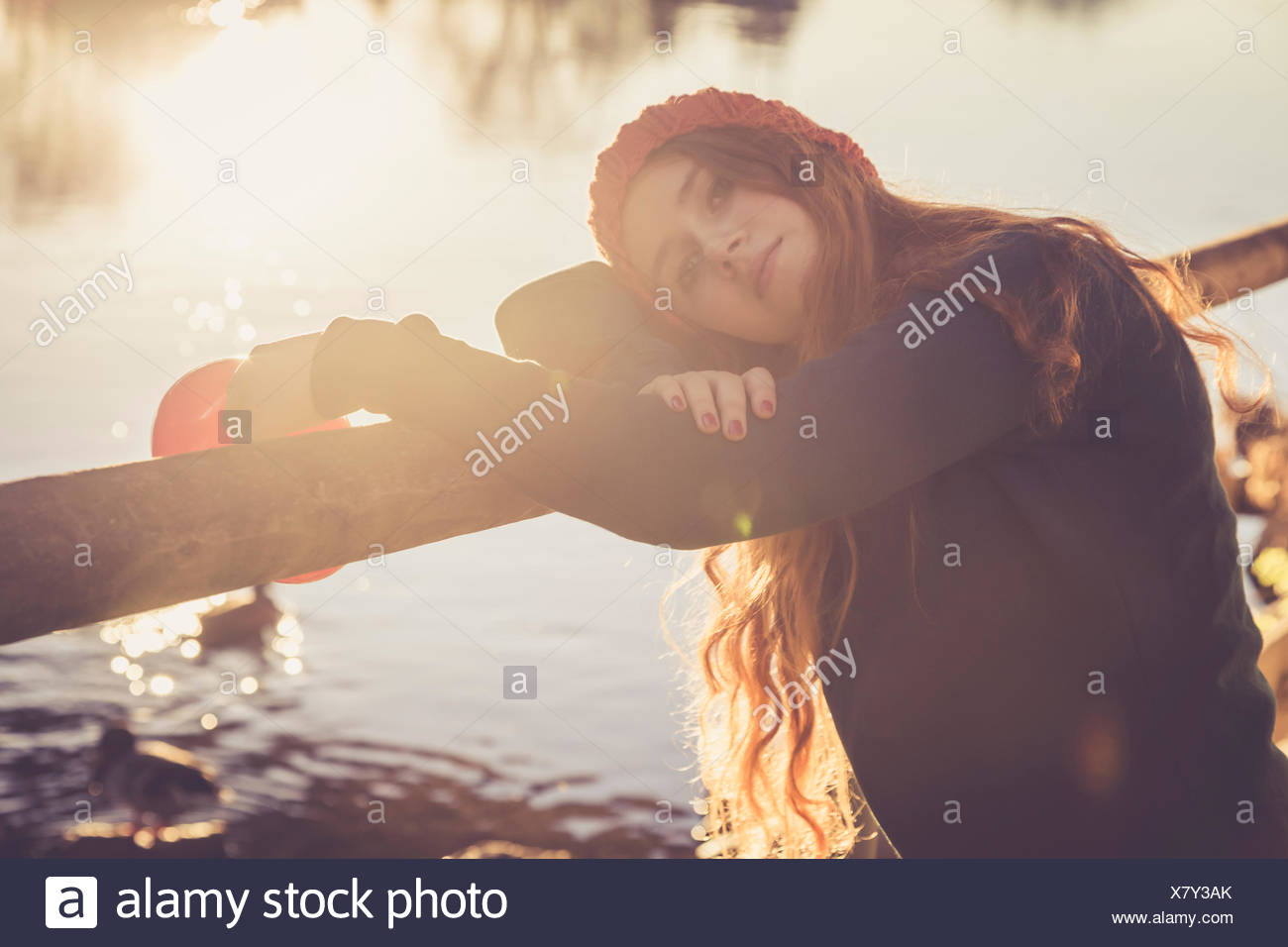 Teenage girl leaning on tree trunk in autumn - Stock Image
