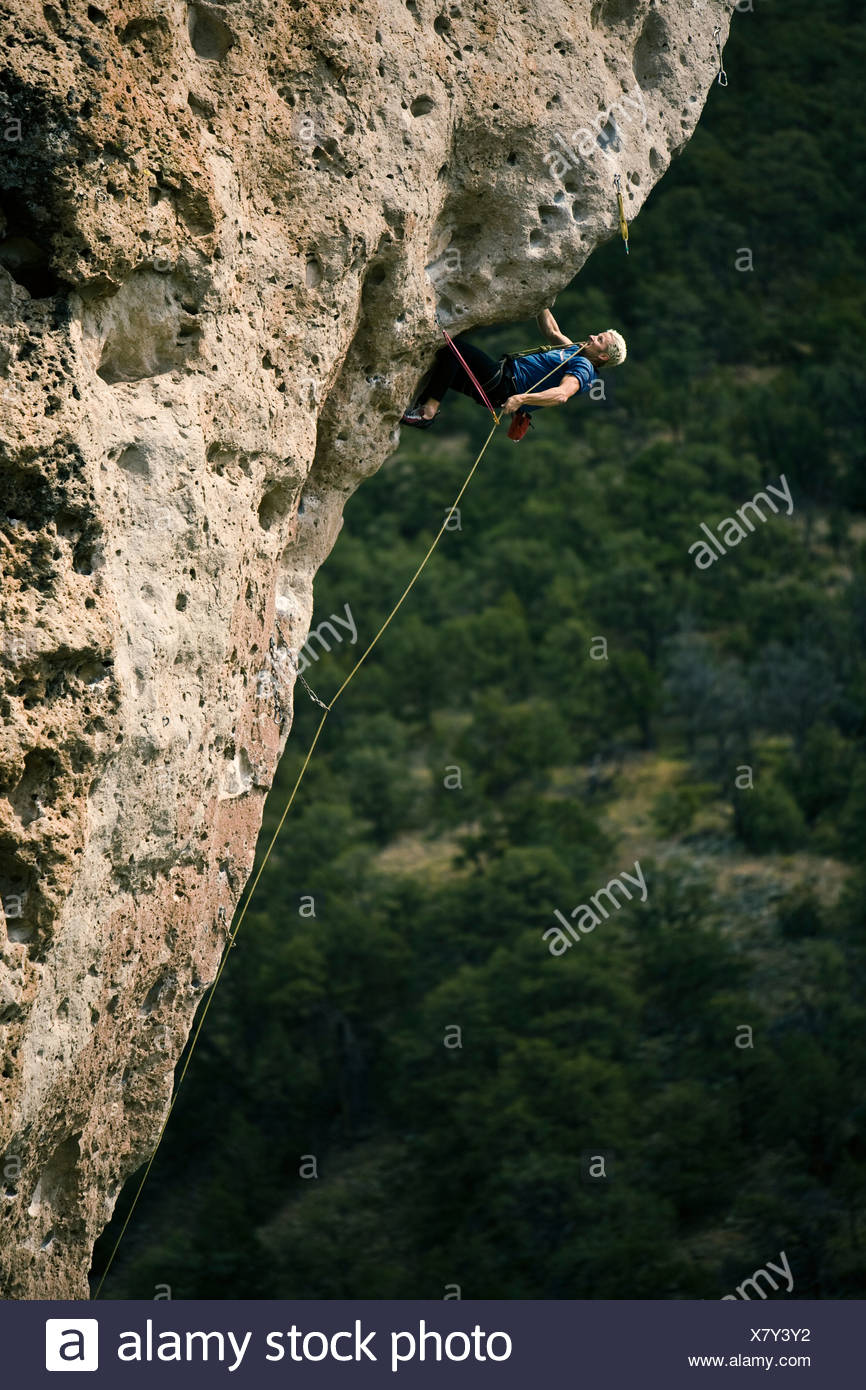 A man desperately clipping a bolt while sport climbing and overhanging prow. - Stock Image
