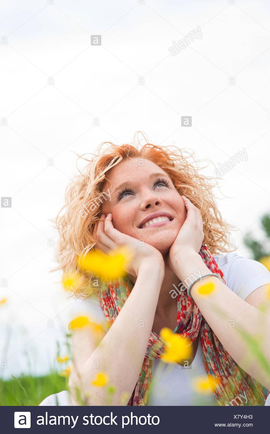 Young woman looking cheerfully upward - Stock Image