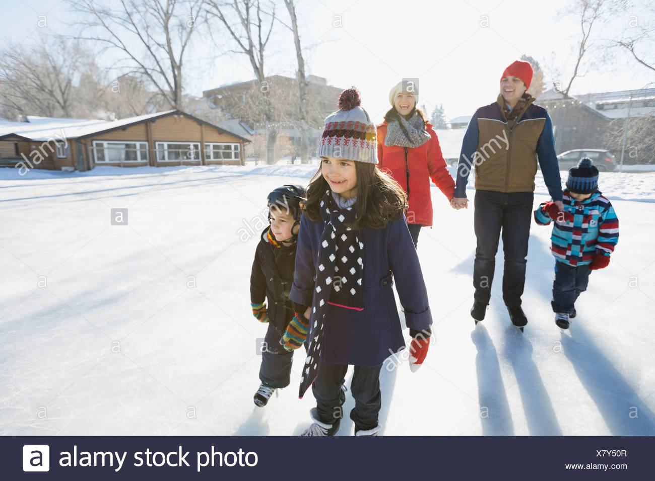 Family ice-skating on outdoor rink together Stock Photo