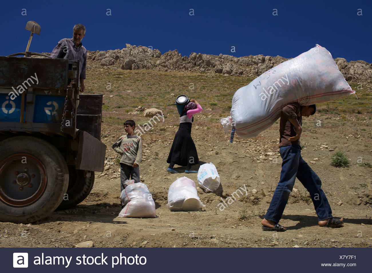 Families carry supplies and household items to their summer home. - Stock Image