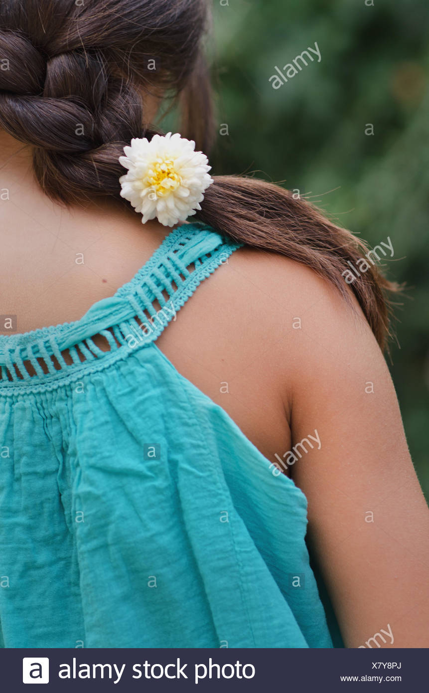 Close-up of girl's (10-11) braid with flower - Stock Image