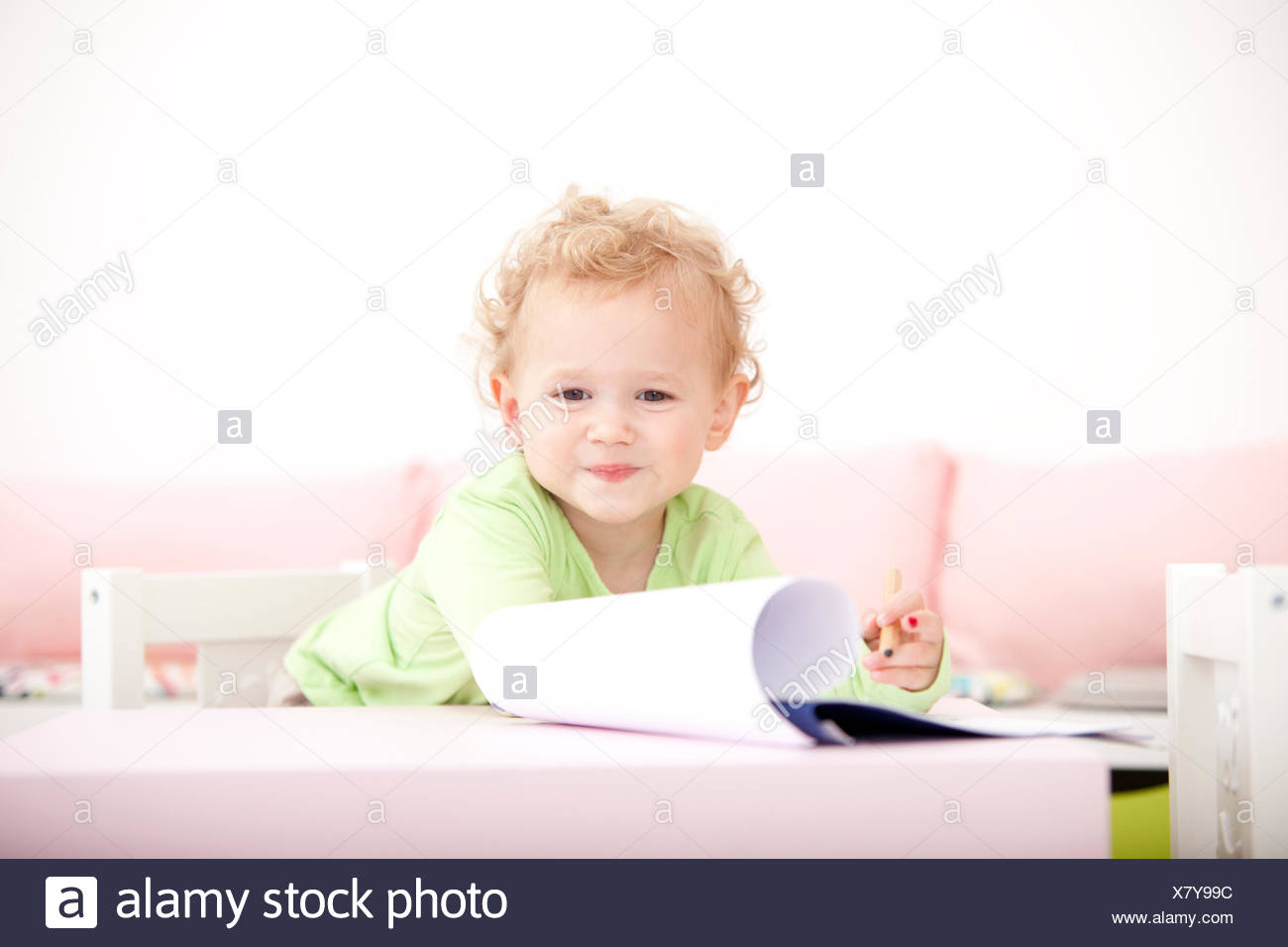 Portrait of little blond girl with coloured pencil - Stock Image