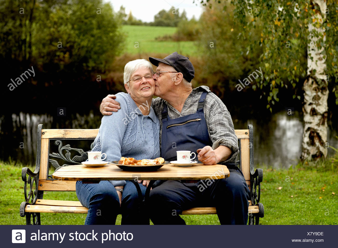 Senior couple sitting at table in back yard Stock Photo