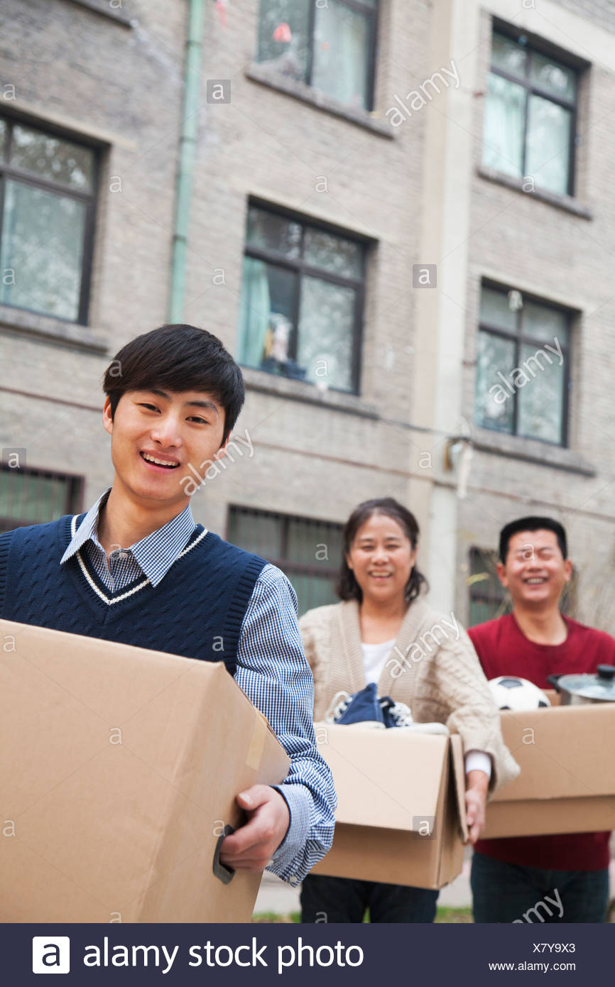 Family moving boxes into a dormitory at college - Stock Image