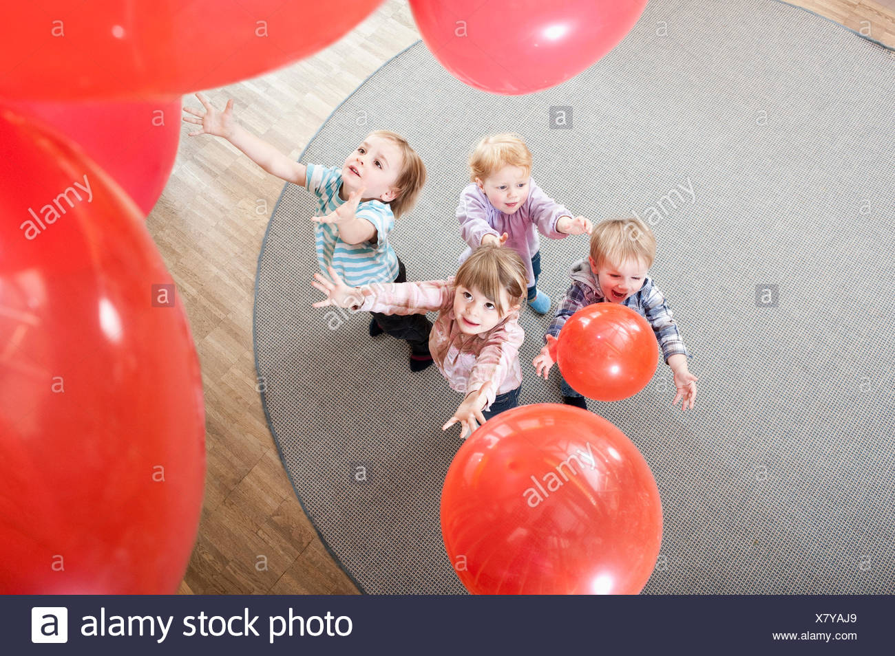 Four kids playing with red balloons in kindergarten, elevated view - Stock Image