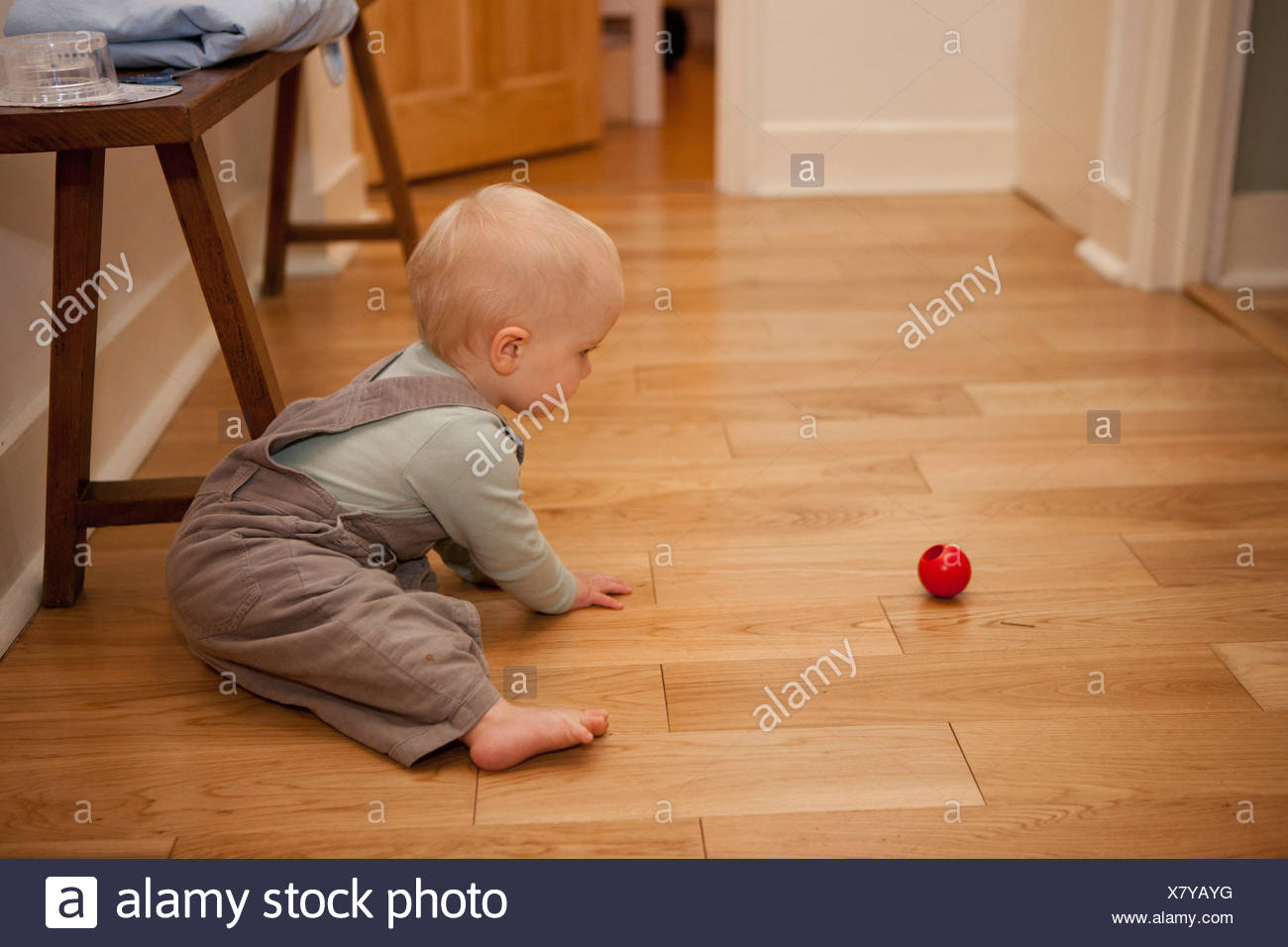 Baby boy playing with ball on the floor - Stock Image