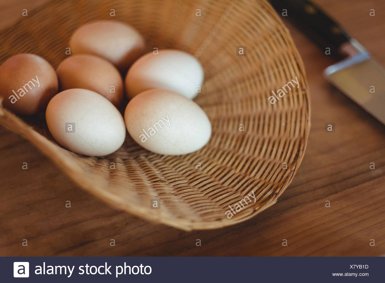 Eggs in wicker basket on wooden table - Stock Image