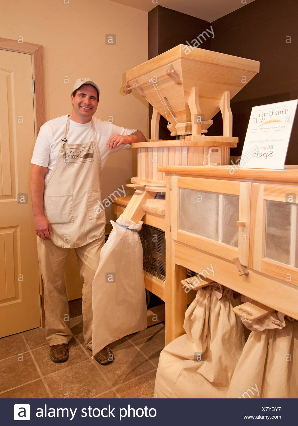 The owner of True Grain Bread in Summerland, British Columbia stands with his flour mill, Okanagan region, Canada - Stock Image