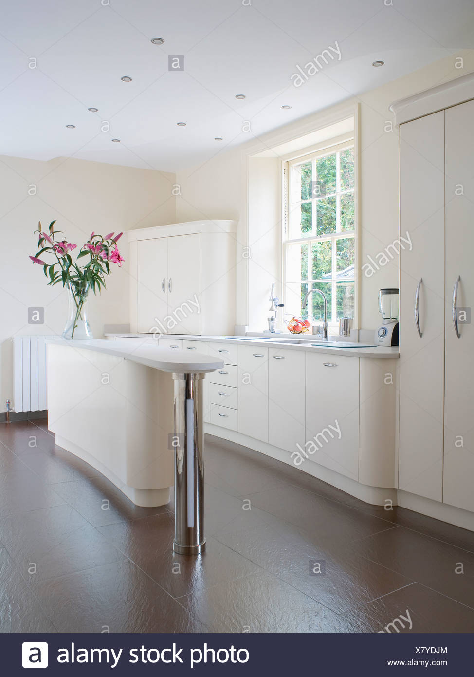 Slate flooring in modern white kitchen with narrow island unit Stock ...