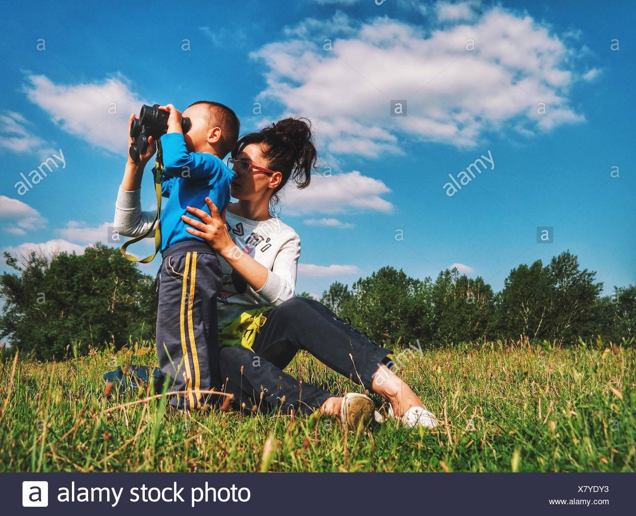 Mother With Boy Looking Through Binoculars At Park Against Sky - Stock Image