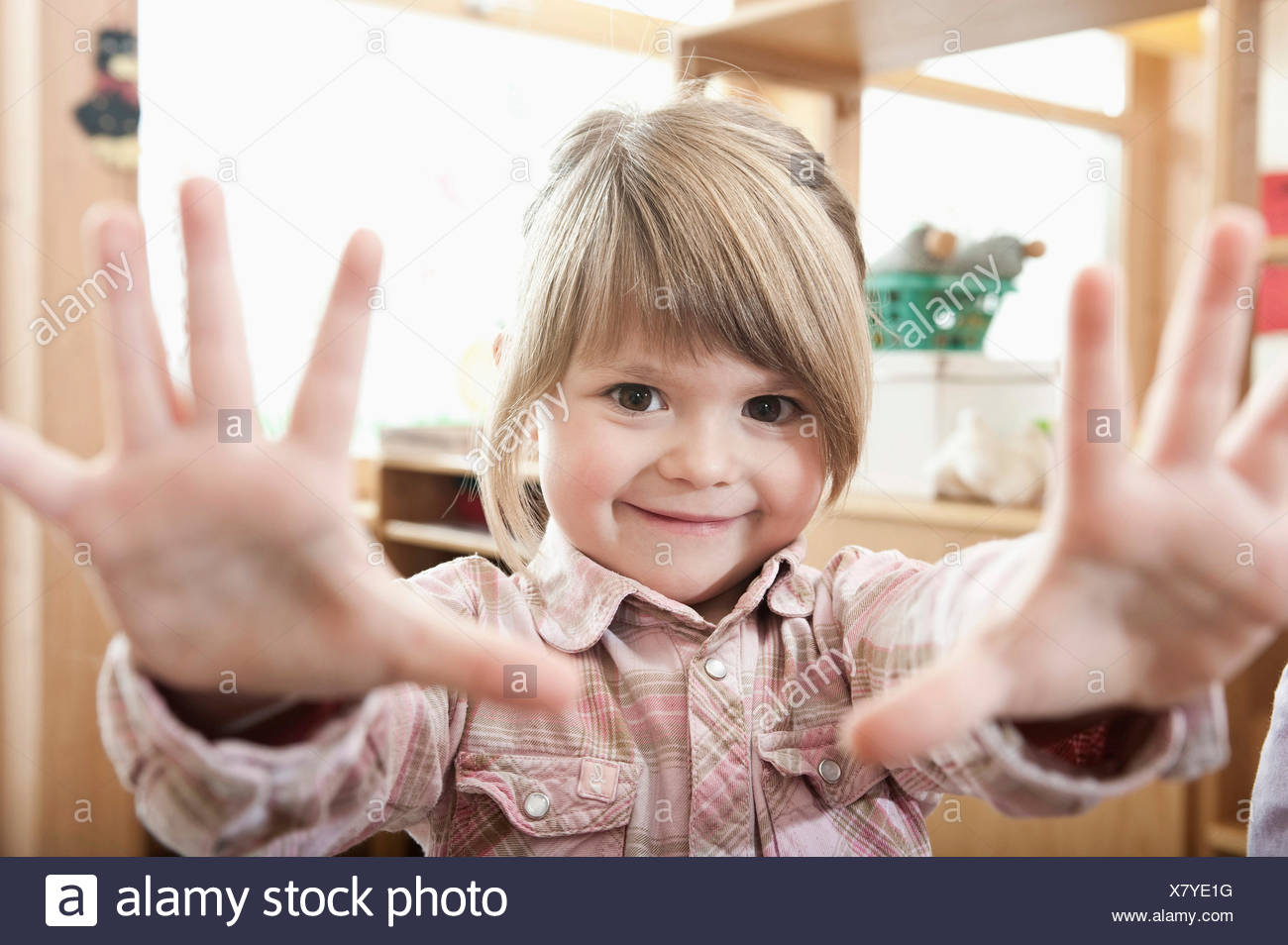 Portrait of smiling little girl showing her hands - Stock Image