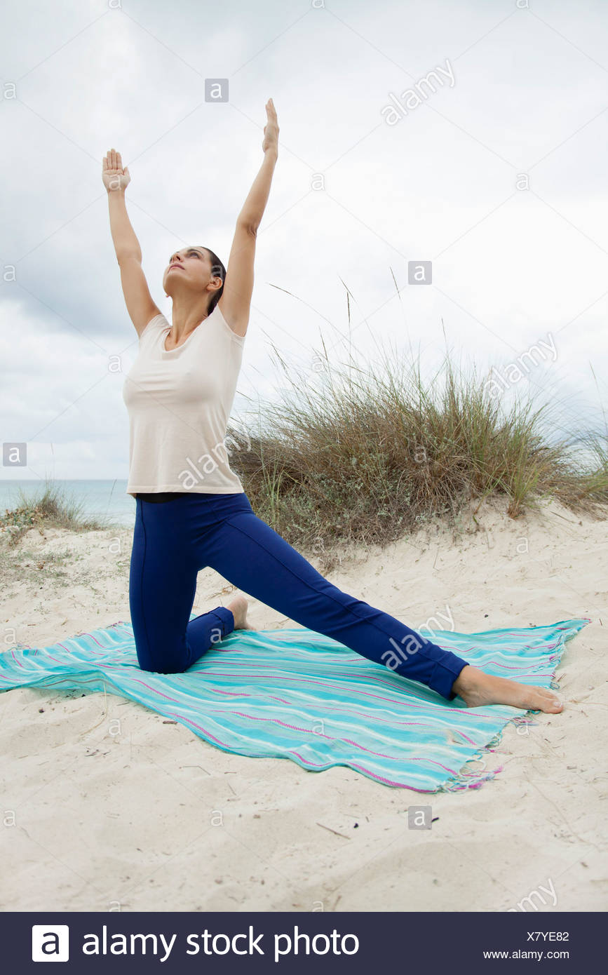 Mature woman practicing yoga on beach Stock Photo