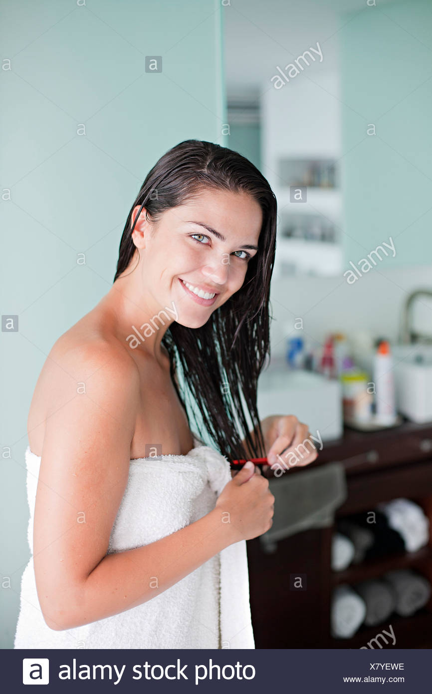 Brunette woman brushing her hair and smiling at camera Stock Photo