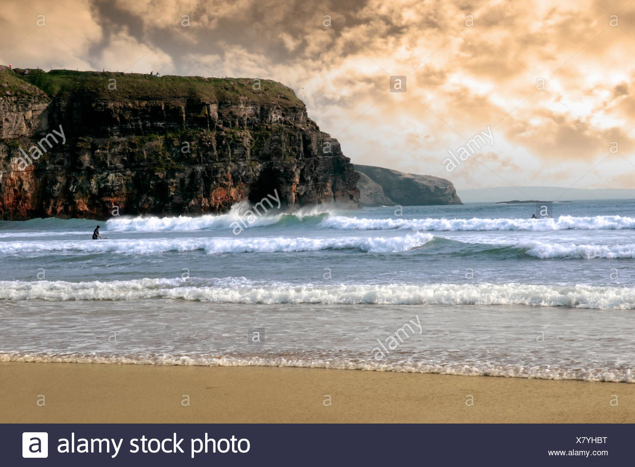 beautiful clean atlantic ocean with surfers catching the waves with cliffs in background on Irelands coast - Stock Image