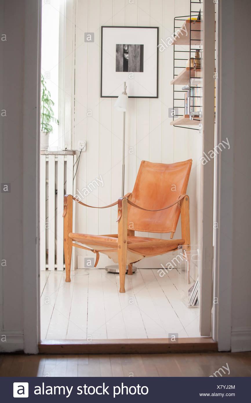 Armchair in corner of white painted room seen through doorway - Stock Image