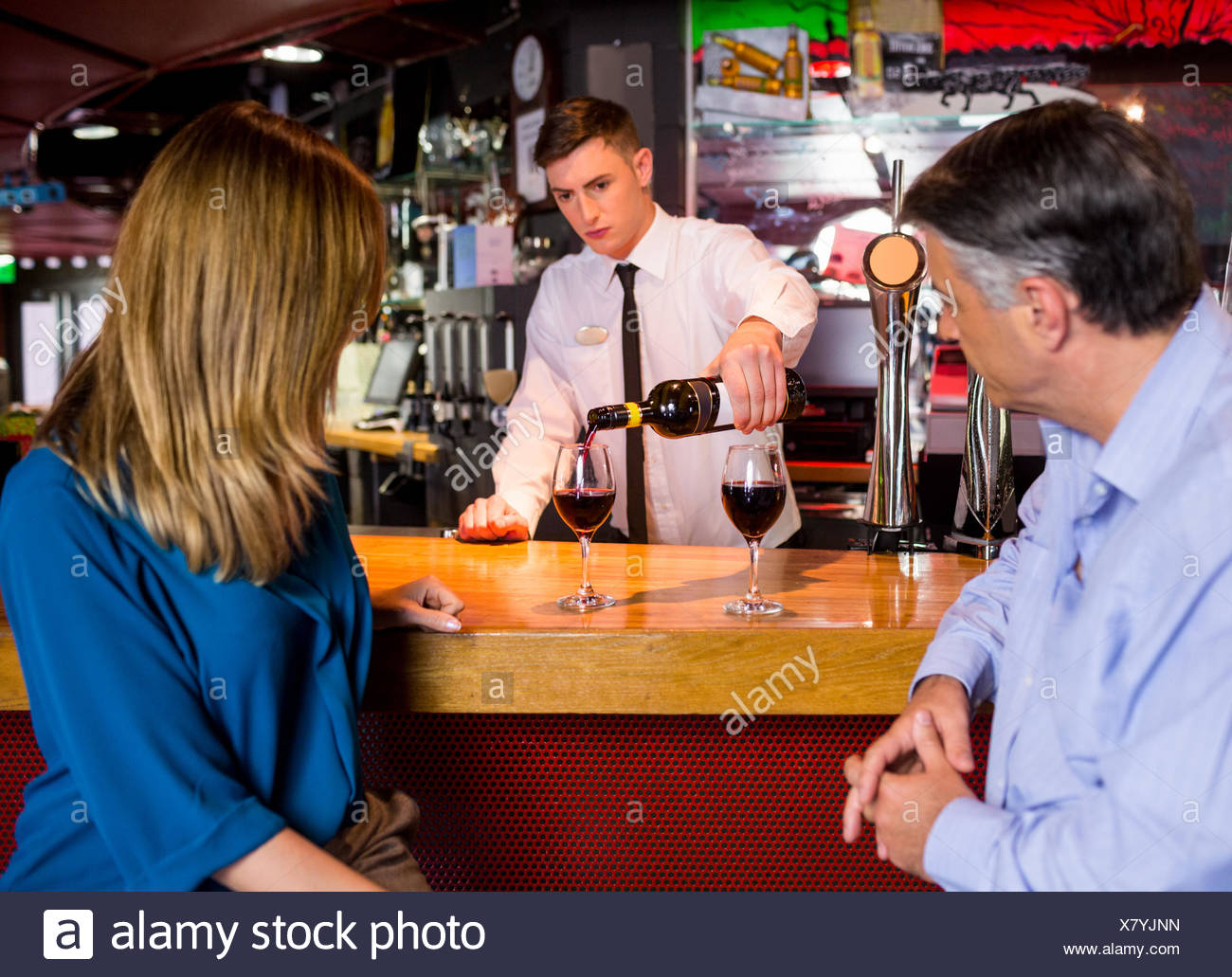 Bartender offering glasses of wine to couple - Stock Image