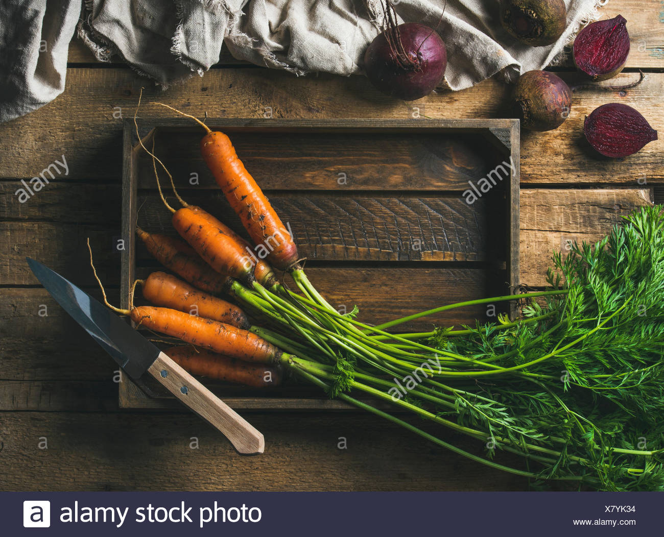 Healthy food cooking background. Vegetable ingredients. Fresh garden carrots and beetroots in wooden tray over rustic wooden bac - Stock Image