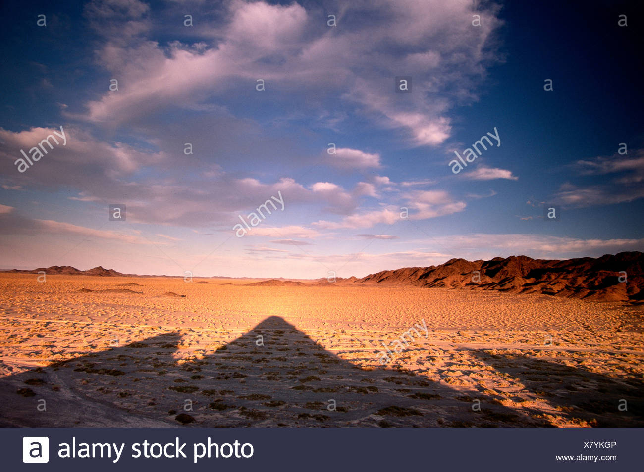 The sun sets behind mountains, which, in turn, cast their long shadows on the valley below, Mongolia. - Stock Image