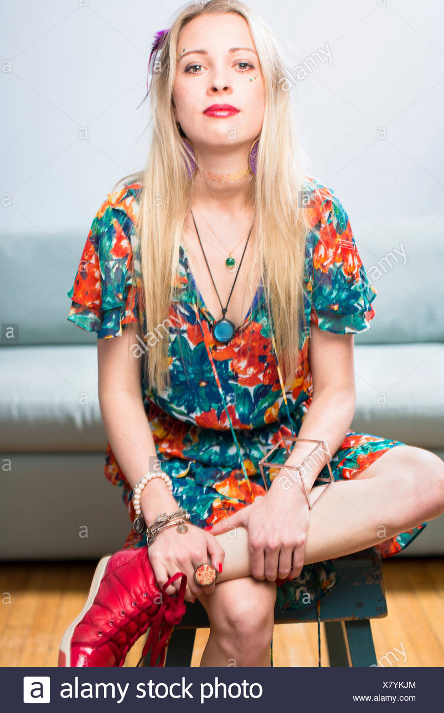 Young woman sitting in floral patterned dress, portrait - Stock Image