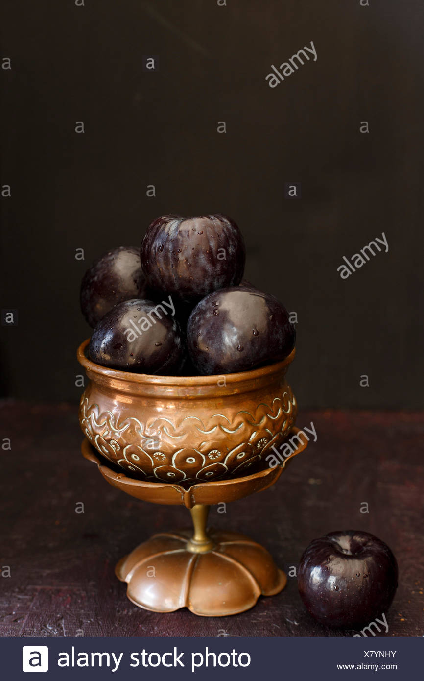Whole Plums in a copper like prop - Stock Image