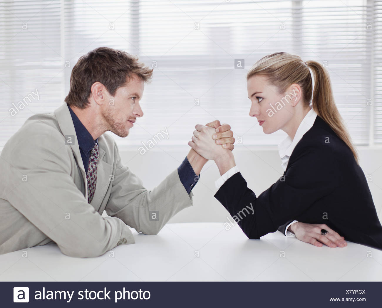 Rival business people arm wrestling - Stock Image