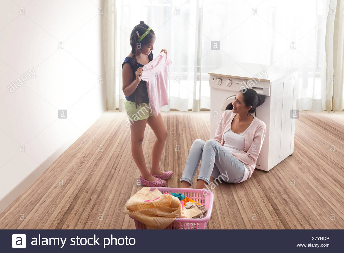 Daughter folding laundry and mother looking at her - Stock Image