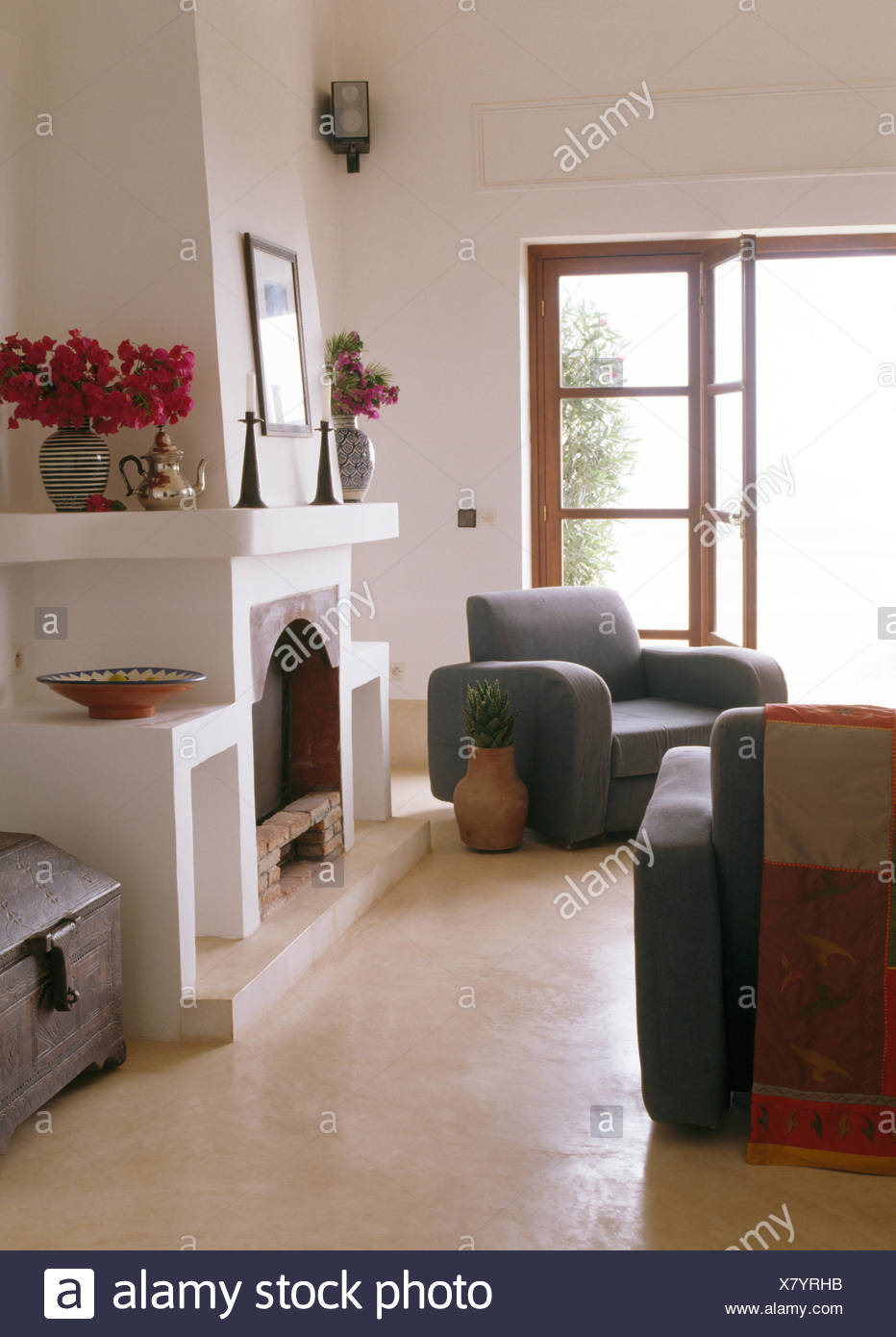 Grey furniture in Moroccan coastal sitting room with white fireplace and polished concrete floor - Stock Image